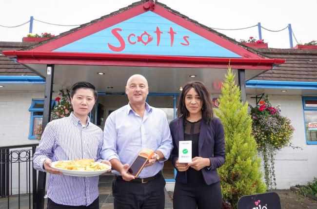 Tony Webster, owner of Scotts fish and chip shop (centre), with JGOO's head of operations Xiaowen Li (left) and senior sales executive Nafisa Meme (right) (PA)